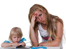 Daughter with mother studying a book Stock Photo