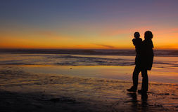 Daughter and mother at sunset 1. Daughter in her mother's arms and mom herself are silhouetted against the sunset at Pacific ocean in San Francisco, California Stock Images