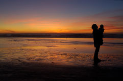 Daughter and mother at sunset 2. Daughter in her mother's arms and mom herself are silhouetted against the sunset at Pacific ocean in San Francisco, California Stock Photography