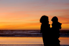 Daughter and mother at sunset 3. Daughter in her mother's arms and mom herself are silhouetted against the gorgeous sunset at Pacific ocean in San Francisco Stock Images