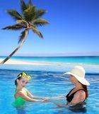 Daughter and mother in swimming pool tropical Stock Image
