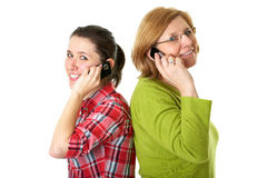 Daughter and mother talks over mobile phones. Happy daughter and mother talks over mobile phones, isolated on white royalty free stock image