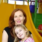 Daughter and mother together in playground slide Stock Images