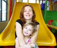 Daughter and mother together in playground slide Royalty Free Stock Images