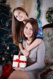 Daughter and mother under Christmas tree Stock Photos