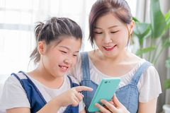 Daughter and mother use smartphone. Daughter and mother use smart phone happily at home stock image