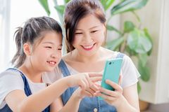 Daughter and mother use smartphone. Daughter and mother use smart phone happily at home stock photo