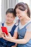 Daughter and mother use smartphone. Daughter and mother use smart phone happily at home royalty free stock image