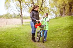 Daughter and mother walk along the shore of the lake with a bike and talk. Family values, education. Daughter and mother walk along the shore of the lake in royalty free stock photos