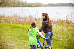 Daughter and mother walk along the shore of the lake with a bike and talk. Family values, education. Daughter and mother walk along the shore of the lake in stock image