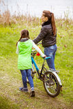 Daughter and mother walk along the shore of the lake with a bike and talk. Family values, education. Daughter and mother walk along the shore of the lake in stock photo