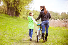 Daughter and mother walk along the shore of the lake with a bike and talk. Family values, education. Daughter and mother walk along the shore of the lake in stock photos