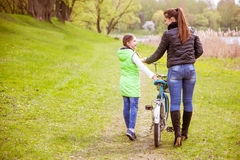 Daughter and mother walk along the shore of the lake with a bike and talk. Family values, education. Daughter and mother walk along the shore of the lake in royalty free stock image