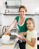 Daughter with mother washing dishes Royalty Free Stock Photography