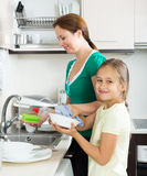 Daughter with mother washing dishes Stock Photography