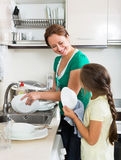 Daughter with mother washing dishes Royalty Free Stock Image