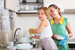 Daughter with mother washing plates Royalty Free Stock Photo