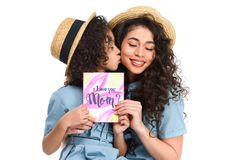 Daughter with mothers day greeting card kissing her mother. Isolated on white royalty free stock photography
