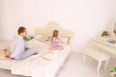 Daughter offense at father who wants to give child flower. Child and father sit on bed, Dad wants to give daughter flower and girl offended. Young happy family Stock Photo