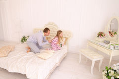 Daughter offense at father who wants to give child flower. Child and father sit on bed, Dad wants to give daughter flower and girl offended. Young happy family Royalty Free Stock Image