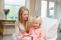 Daughter opening a present from mum Stock Image
