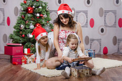 Daughter opens a gift at Christmas tree Stock Photo