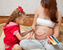 A daughter is painting on her mother`s belly Royalty Free Stock Image
