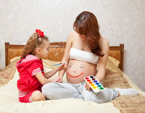 A daughter is painting on her mother`s belly Stock Photo