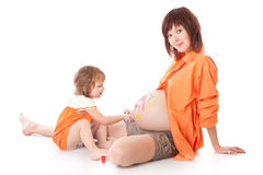 Daughter is painting on her mother's belly Royalty Free Stock Photos