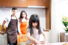 Daughter and parent preparing the bake. Daughter and parent preparing the bake stock photography