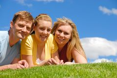 Daughter with parents. On grass area Royalty Free Stock Photos