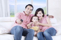 Daughter and parents watching TV Stock Photography