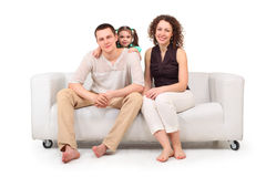 Daughter and parents on white leather sofa stock image