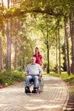 Daughter in the park pushing enjoying senior man in wheelchair Royalty Free Stock Photography