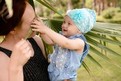 The daughter is played with a palm leaf and her mother`s nose. The girl holds the baby in her arms and plays with her palm leaf, the child is happy and happy royalty free stock image