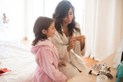 Daughter playing with her mother jewellery Royalty Free Stock Images
