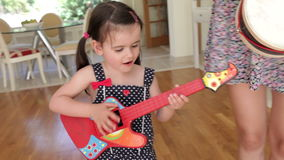 Daughter plays toy guitar and  Royalty Free Stock Images