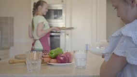 Daughter pouring milk into a glass, and happy mom pulling out freshly baked buns from the oven in cozy kitchen. Cute daughter pouring milk into a glass, and stock footage