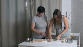 Daughter pregnant and mother cook together in the kitchen, daughter helps mother knead dough for pancakes or cookies.  stock video