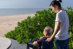 Daughter push the wheel-chair forward for her mother in front of the beach. This shows the warmth relationship in family. This can be related with any article stock photography