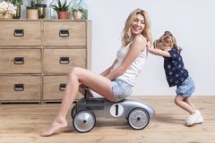 Daughter pushes mother sitting on toy car royalty free stock photos