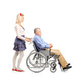 Daughter pushing her dad in a wheelchair Royalty Free Stock Image