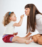 Daughter put on lipstick. On gray background Stock Photos