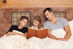 Daughter reading book to brother and father - happy family stock photos