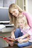 Daughter Reading Book Whilst Mother Works In Home Office Stock Images