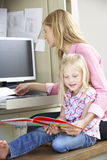 Daughter Reading Book Whilst Mother Works In Home Office Royalty Free Stock Photo