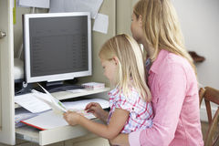 Daughter Reading Book Whilst Mother Works In Home Office Royalty Free Stock Images