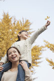 Daughter Riding Piggy-Back on Mother's Shoulders Enjoying Autumn Leaves Stock Image
