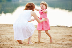 Daughter running to mother in summer. Happy daughter running to mother on a beach in summer Royalty Free Stock Photos