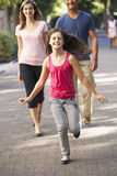 Daughter Runs Ahead Of Parents On Walk Through Summer Park Royalty Free Stock Photography